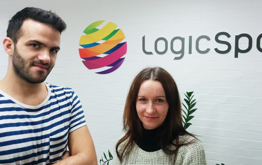 Alex and Florentina in front of LogicSpot logo